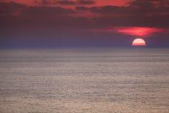 Красный рассвет над синью видит стоковое фото rf
