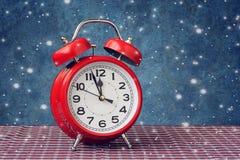 Красный ретро будильник на часах ` 12 o и летание идут снег Стоковые Фотографии RF
