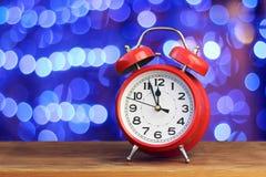 Красный ретро будильник на часах ` 12 o Стоковые Фото