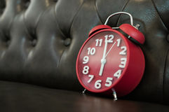 Красный ретро будильник на софе Стоковые Фото
