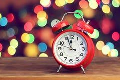 Красный ретро будильник на 12 o& x27; часы на предпосылке с b Стоковая Фотография