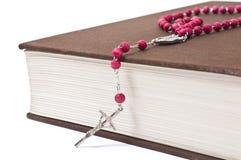 Красный розарий на книге Стоковое Изображение