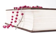 Красный розарий на книге Стоковые Фото
