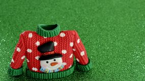 Красный свитер с зелеными тумаками воротника и рукава стоковые изображения
