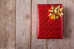Красный смычок на деревянной таблице, взгляд сверху золота подарочной коробки Стоковое Изображение RF