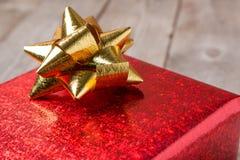 Красный смычок на деревянной таблице, конец золота подарочной коробки вверх Стоковая Фотография RF