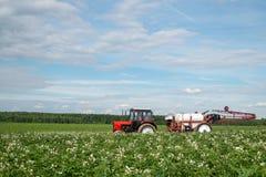 Красный спрейер трактора в поле стоковые изображения