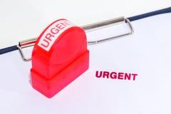 Красный срочный штемпель на белой бумаге с резиновыми stamper и доской сзажимом для бумаги Стоковое Изображение RF