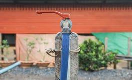 Красный старый винтажный водопроводный кран с резиновой трубкой на сельском доме стоковая фотография