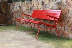 Красный стенд около каменной стены Стоковое Изображение