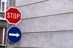 Красный стоп знака и голубая стрелка знака Стоковые Изображения