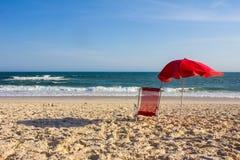 Красный стул и красный зонтик на солнечный день на пляже Стоковое фото RF