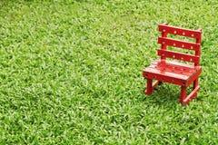 Красный стул на зеленой траве Стоковая Фотография RF