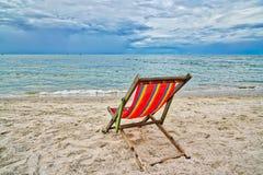 Красный стул смотря на море на пляже стоковое изображение rf