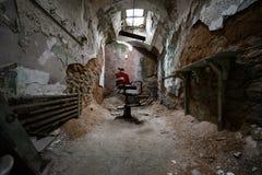 Красный стул парикмахера в тюремной камере стоковое изображение rf
