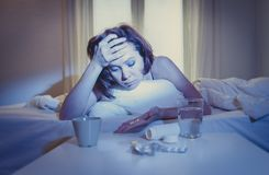 Красный с волосами больной женщины в кровати с медициной Стоковое Изображение