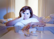 Красный с волосами больной женщины в кровати с медициной Стоковое фото RF