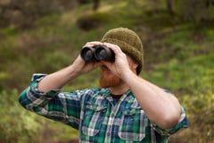 Красный с волосами человек смотря ход бинокулярное Стоковое Изображение