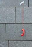 Красный телефон вися вниз связанный тесьмой к стене Стоковая Фотография RF