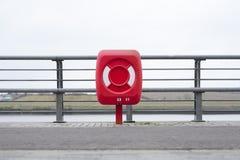 Красный томбуй кольца безопасности жизни на гавани гавани порта предотвращает потонуть в море не может поплавать Стоковые Фотографии RF