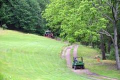 Красный трактор вытягивая диско через путь грязи пока аллигатор следовать Стоковая Фотография RF