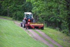 Красный трактор вытягивая диско через путь грязи Стоковые Изображения RF