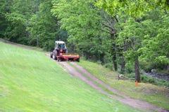Красный трактор вытягивая диско через путь грязи Стоковое Фото