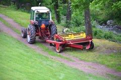 Красный трактор вытягивая диско через путь грязи Стоковая Фотография RF