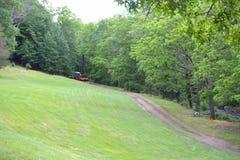 Красный трактор вытягивая диско через путь грязи Стоковое Изображение