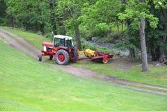 Красный трактор вытягивая диско через путь грязи Стоковая Фотография