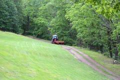 Красный трактор вытягивая диско через путь грязи Стоковые Фото