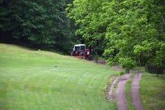 Красный трактор вытягивая диско через путь грязи Стоковое фото RF