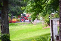 Красный трактор вытягивая диско через путь грязи Стоковые Фотографии RF