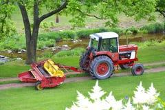 Красный трактор вытягивая диско через путь грязи Стоковые Изображения