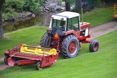 Красный трактор вытягивая диско через путь грязи Стоковое Изображение RF