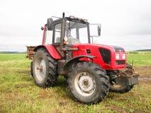 Красный трактор в поле Стоковые Фото