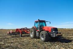Красный трактор в поле Стоковые Изображения