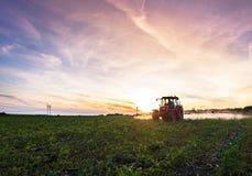 Красный трактор культивируя поле под голубым небом Стоковые Изображения