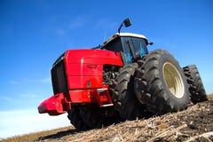 Красный трактор работая в поле Стоковое фото RF
