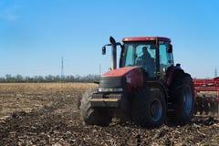 Красный трактор работая в поле Стоковые Изображения RF