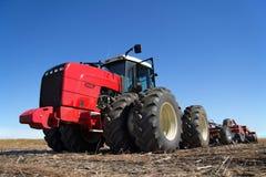 Красный трактор работая в поле Стоковая Фотография RF