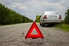 Красный треугольник автомобиля на дороге Треугольник автомобиля предупреждающий на дороге против города в вечере Нервное расстрой Стоковое фото RF