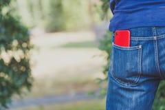 Красный умный телефон в кармане стоковые изображения rf