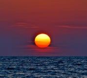 красный фиолетовый заход солнца на воде Стоковая Фотография