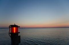 Красный фонарик морем на заходе солнца Стоковые Фотографии RF