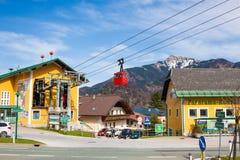 Красный фуникулер приходя назад к станции фуникулера Zwoelferhorn в высокогорном городке StGilgen на Wolfgangsee, Австрии Стоковое Фото