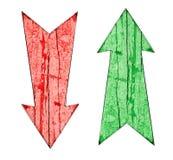 Красный цвет вниз и зеленый цвет вверх по винтажным деревянным стрелкам направления на треснутый и шелушение покрасили деревянный Стоковое Изображение