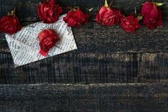 Красный цвет высушил розы и конверт на деревянном столе Стоковые Изображения
