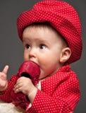 красный цвет девушки еды младенца красивейшим одетьнный платьем Стоковая Фотография