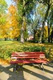 Красный цвет, деревянная скамья в парке в осени Стоковые Фото